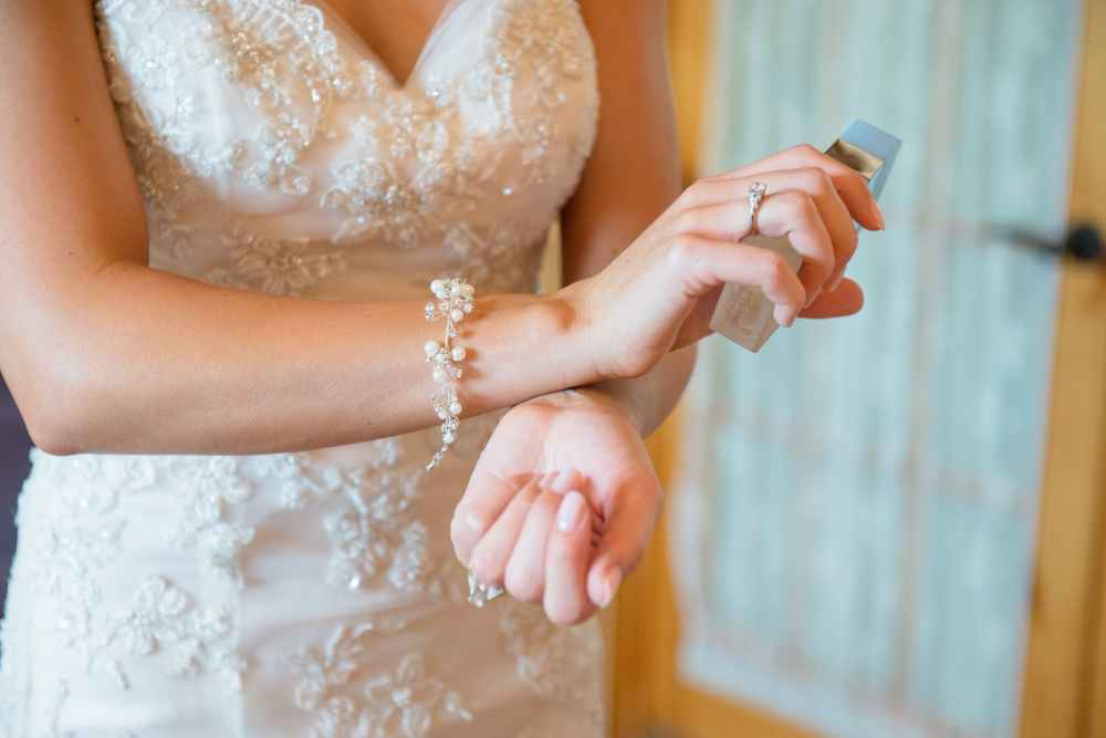 close up photo of woman rubbing perfume on her wrist
