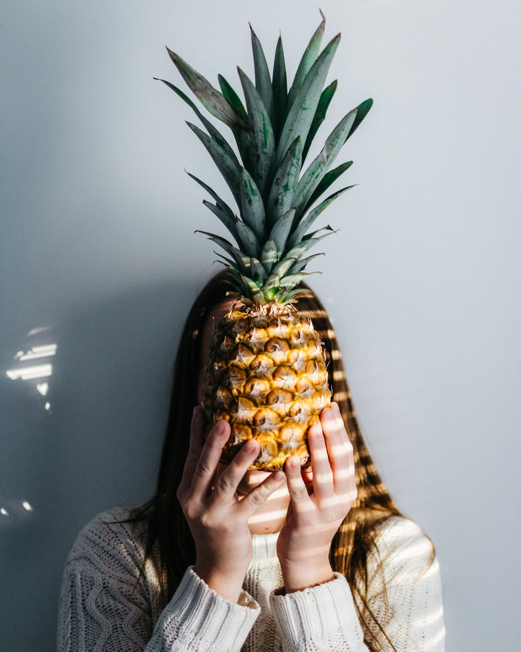 photo of person holding pineapple fruit in front of face